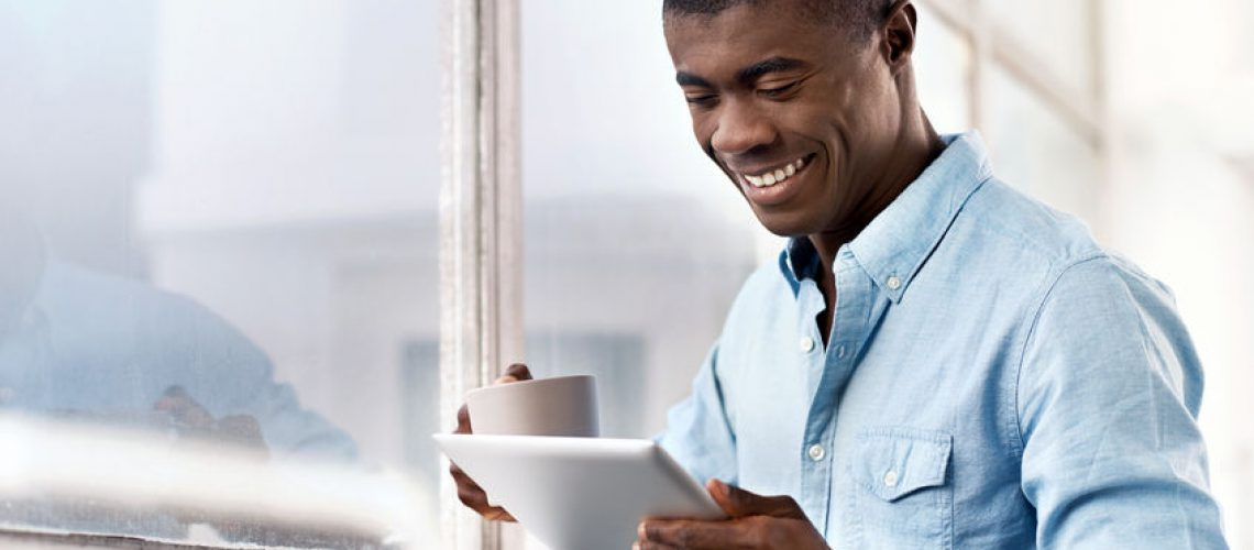40834406 - young successful black african man with morning coffee and tablet computer checking on news of investments